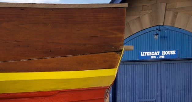 Image of a red and yellow boat with a blue door to a lifeboat house in the background.