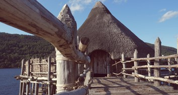 Exterior view of the Scottish Crannog Centre, a thatched wooden building on stilts on the Loch Tay